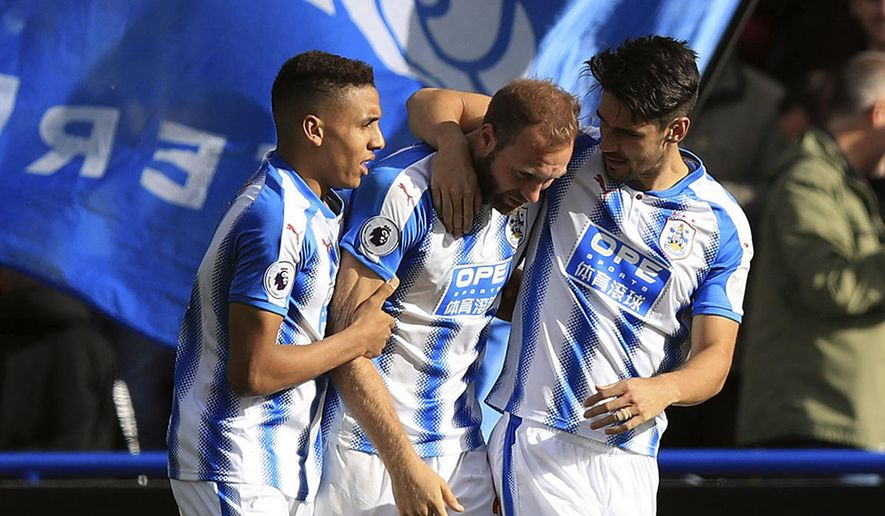 Huddersfield Town's Laurent Depoitre, centre,  celebrates with his team-mates after scoring his side's first goal, during the English Premier League soccer match between Huddersfield and Leicester City, at the John Smith's Stadium, in Huddersfield, England, Saturday, Sept. 16, 2017. (Mike Egerton/PA via AP)