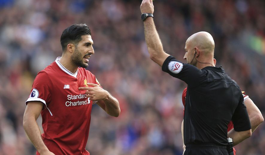 Liverpool's Emre Can, left,  is shown a yellow card by referee Roger East during the English Premier League soccer match between Liverpool and Burnley, at Anfield, in Liverpool, England, Saturday, Sept. 16, 2017. (Peter Byrne/PA via AP)