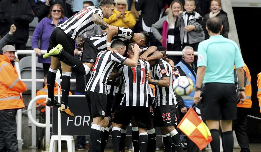 Newcastle United's Jamaal Lascelles, obscured, celebrates with team-mates after scoring his team's second goal against Stoke City during their English Premier League soccer match at St James' Park in Newcastle, England, Saturday Sept. 16, 2017. (Owen Humphreys/PA via AP)