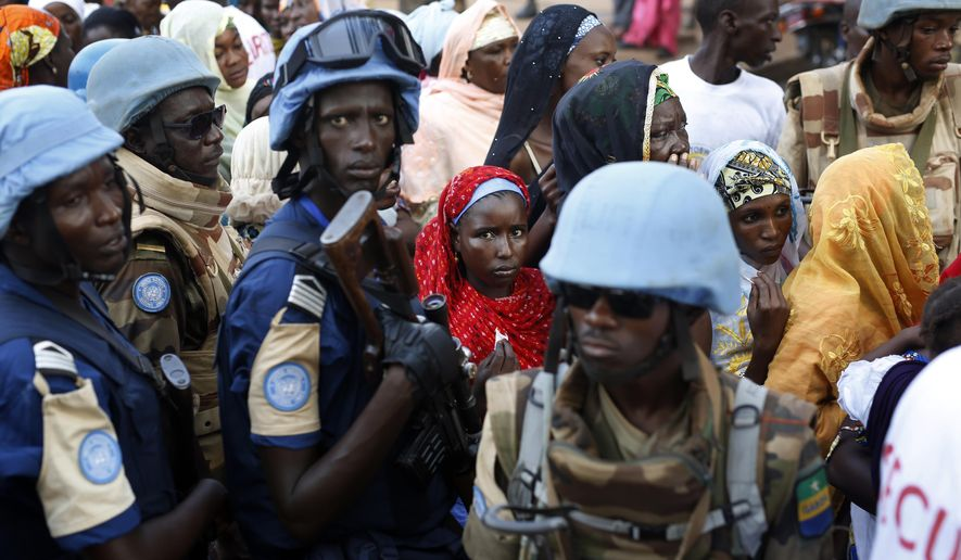 FILE- In this Nov. 30, 2015 file photo, UN soldiers stand near Muslims faithful queuing to enter the Central Mosque on the occasion of Pope Francis' visit, in Bangui's Muslim enclave of PK5, Central African Republic. The United Nations peacekeeping mission in the Central African Republic is requesting about 750 more troops, according to a confidential cable obtained by the Associated Press. (AP Photo/Jerome Delay, File)