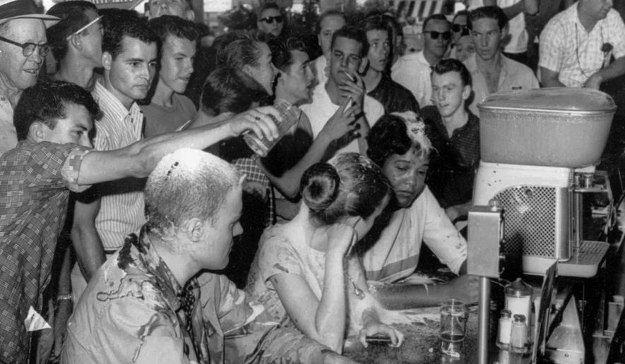 FILE - In this May 28, 1963 file photograph, a group of white people pour sugar, ketchup and mustard over the heads of Tougaloo College student demonstrators at a sit-in demonstration at a Woolworth's lunch counter in downtown Jackson, Miss. Seated at the counter, from left, are Tougaloo College professor John Salter,and students Joan Trumpauer and Anne Moody. Anne Moody, a  civil rights activist who wrote about challenging segregation in the South is being honored in her hometown, two years after her death.   (Fred Blackwell/The Clarion-Ledger via AP)