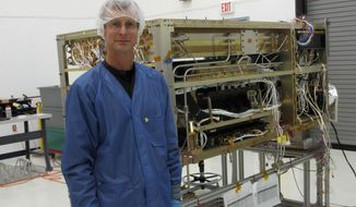 This March 24, 2015, photo provided by NASA shows  Dr. Scott Nutter who helped assemble and test the ISS-CREAM instrument at NASA's Wallops Flight Facility in a clean room environment.  On Aug. 14, the International Space Station-Cosmic Ray Energetics and Mass (ISS-CREAM) instrument, an experiment that Nutter and an international team of researchers started seven years ago, was placed on a rocket and launched into space. (Alice Nutter via AP)