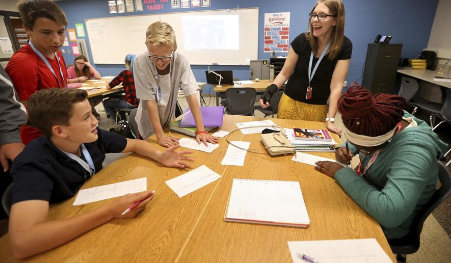 In this Thursday, Aug. 31, 2017, photo, Angie Bishop helps students during a honors algebra II class at Senior High School in Dubuque, Iowa. Bishop has implemented a flipped classroom model, where students learn their lessons outside the classroom and then practice what they learned while they are in school. (Jessica Reilly/Telegraph Herald via AP)