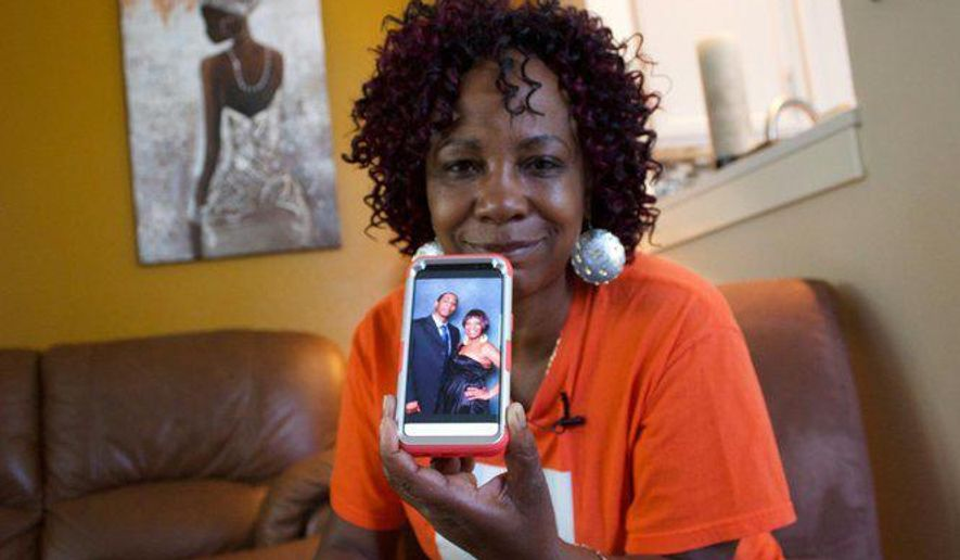 """In this September 2017 photo, Lucy Mashia poses for a portrait in Portland, Ore., while showing one of her favorite photos of her son,  Leonard James """"L.J."""" Irving, who was killed in a gang related shooting. Portland police have handled 81 gang shootings so far this year - and that's actually a hopeful number for the officers who work on a team dedicated to trying to keep the violence at bay, their boss says.  (Olivia Dimmer/The Oregonian via AP)"""
