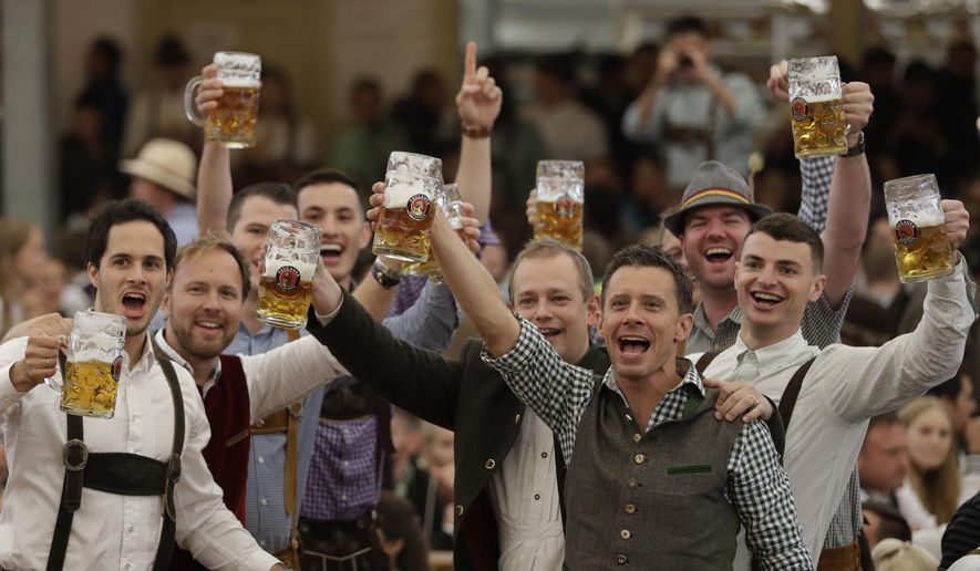 """Young men celebrate the opening of the 184th Oktoberfest beer festival in the """"Paulaner brewery"""" tent in Munich, Germany, Saturday, Sept. 16, 2017. The world's largest beer festival was held from Sept. 16 until Oct. 3. (AP Photo/Matthias Schrader) ** FILE **"""