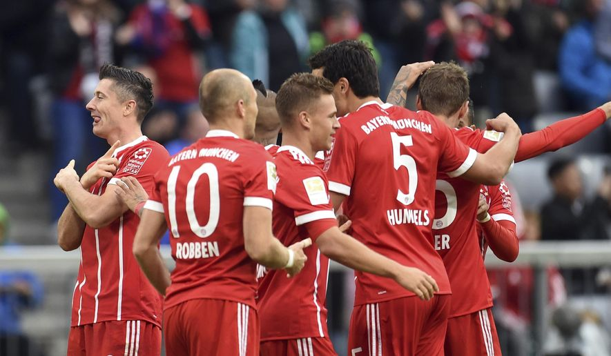 Munich's Robert Lewandowski, left, celebrates his goal together with his team during the first division Bundesliga soccer match between Bayern Munich and FSV Mainz 05 in Munich, Germany, Saturday, Sept. 16, 2017. (Andreas Gebert/dpa via AP)