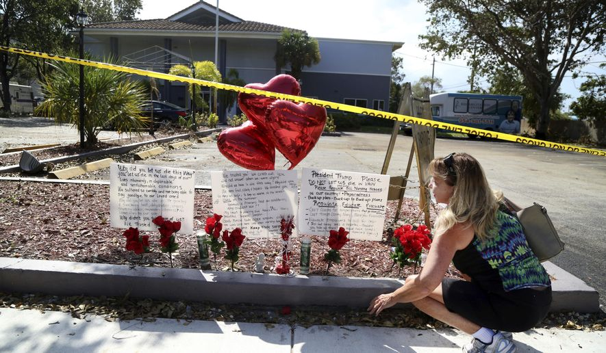 FILE - In this Thursday, Sept. 14, 2017 file photo, Janice Connelly of Hollywood, sets up a makeshift memorial in memory of the senior citizens who died in the heat at The Rehabilitation Center at Hollywood Hills, Fla. Multiple people died and patients had to be moved out of the facility, many of them on stretchers or in wheelchairs. Authorities have launched a criminal investigation to figure out what went wrong and who, if anyone, was to blame. (Carline Jean /South Florida Sun-Sentinel via AP, File)
