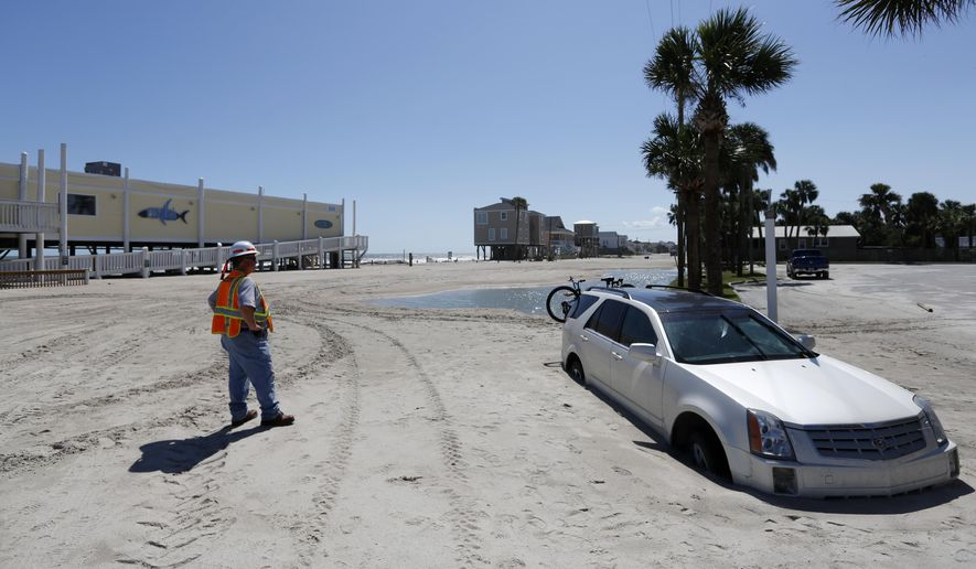 Greg Smith with the South Carolina Department of Transportation waits to remove a car stuck in Palmetto Blvd., in Edisto Beach, S.C., Tuesday, Sept. 12, 2017, as the road is covered in several feet of sand after Tropical Storm Irma hit. Edisto Beach suffered the same fate last year with Hurricane Matthew. (AP Photo/Mic Smith)