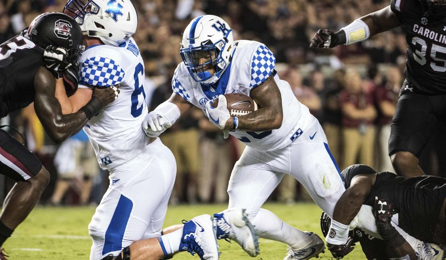 Kentucky running back Benny Snell Jr., center, runs the ball during the first half of an NCAA college football game against South Carolina, Saturday, Sept. 16, 2017, in Columbia, S.C. (AP Photo/Sean Rayford)