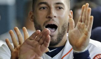Houston Astros' George Springer is congratulated in the dugout after scoring a run against the Seattle Mariners during the second inning of a baseball game Saturday, Sept. 16, 2017, in Houston. (AP Photo/David J. Phillip)
