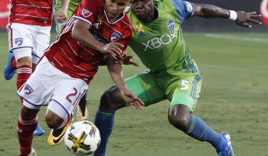 FC Dallas midfielder Michael Barrios (21) avoids being tripped by Seattle Sounders defender Nouhou Tolo (5) during the first half of an MLS soccer match Saturday, Sept. 16, 2017, in Frisco, Texas. (Stewart F. House/The Dallas Morning News via AP)
