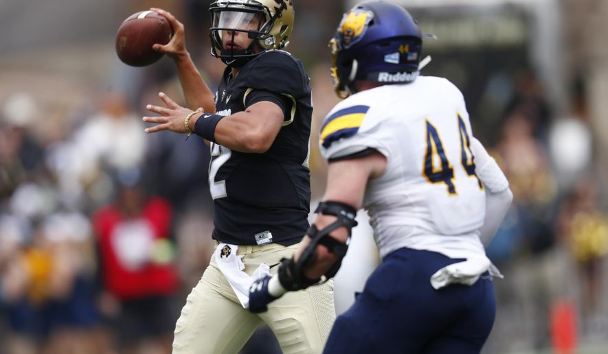 Colorado quarterback Steven Montez, left, throws a pass over Northern Colorado linebacker Henry Stelzner in the first half of an NCAA college football Saturday, Sept. 16, 2017, in Boulder, Colo. (AP Photo/David Zalubowski)