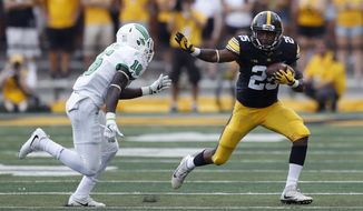 Iowa running back Akrum Wadley runs from North Texas defensive back Kemon Hall, left, after catching a pass during the first half of an NCAA college football game, Saturday, Sept. 16, 2017, in Iowa City, Iowa. (AP Photo/Charlie Neibergall)