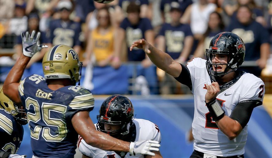 Oklahoma State quarterback Mason Rudolph (2) passes over Pittsburgh linebacker Elijah Zeise (25) in the first quarter of an NCAA football game, Saturday, Sept. 16, 2017, in Pittsburgh. Oklahoma State won 59-21.(AP Photo/Keith Srakocic)