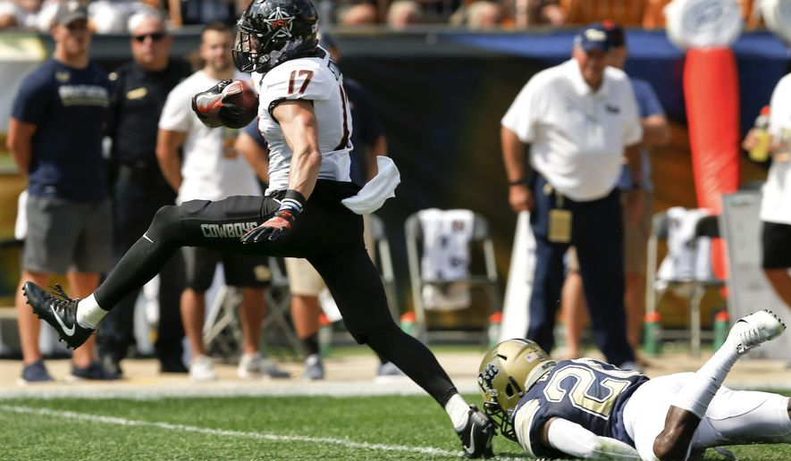 Oklahoma State wide receiver Dillon Stoner (17) breaks away from Pittsburgh defensive back Dennis Briggs (20) after making a catch to run it in for a touchdown in the first quarter of an NCAA college football game, Saturday, Sept. 16, 2017, in Pittsburgh. (AP Photo/Keith Srakocic)
