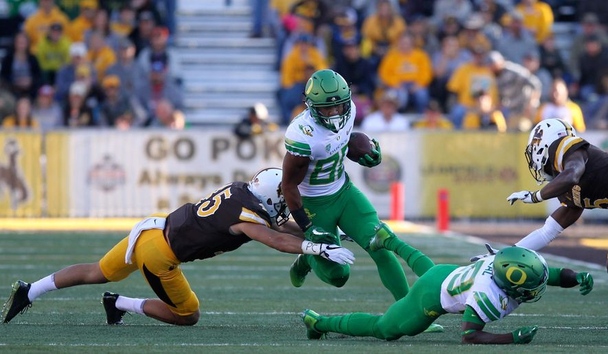 Oregon wide receiver Johnny Johnson III trips over runs past an attempted tackle from Wyoming linebacker Adam Pilapil (45) while Oregon wide receiver Darrian McNeal (89) blocks Wyoming cornerback Rico Gafford (5) during the first half of an NCAA college football game in Laramie, Wyo., Saturday, Sept.16, 2017. (AP Photo/Shannon Broderick)