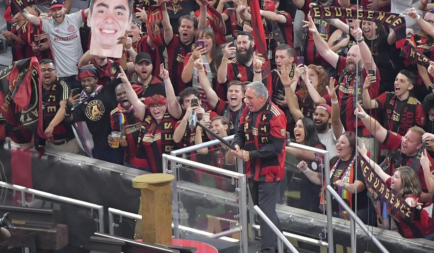 Arthur Blank, owner of Atlanta United FC, hammers in Atlanta United's golden spike in front of record-breaking crowd before an MLS soccer match against Orlando City, Saturday, Sept. 16, 2017, in Atlanta. (Hyosub Shin/Atlanta Journal-Constitution via AP)