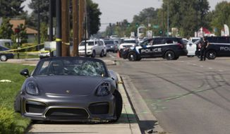 Police block off the scene were the driver of a Porsche injured eight bystanders after losing control of the sports car near the Boise Spectrum 21 theaters Saturday, Sept. 16, 2017 in Boise, Idaho. Police say the driver of the gray Porsche accelerated rapidly while leaving the Cars and Coffee event but lost control and ran into the nearby crowd. Ambulances took six people to hospitals and two others were taken by private vehicles. Police didn't provide any names or conditions.  (Darin Oswald/Idaho Statesman via AP)