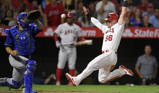 Los Angeles Angels' Kole Calhoun, right, scores on a single by Andrelton Simmons as Texas Rangers catcher Brett Nicholas takes a late throw during the fourth inning of a baseball game, Friday, Sept. 15, 2017, in Anaheim, Calif. (AP Photo/Mark J. Terrill)