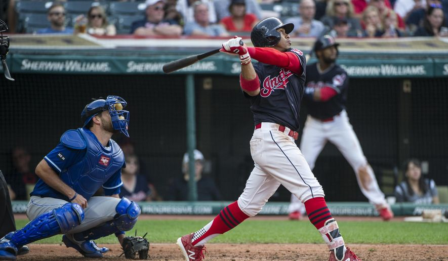 Cleveland Indians' Francisco Lindor and Kansas City Royals' Drew Butera watch his two-run double during the sixth inning of a baseball game in Cleveland, Saturday, Sept. 16, 2017. (AP Photo/Phil Long)