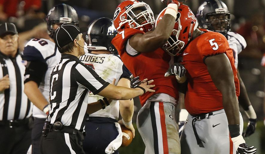 Georgia outside linebacker Lorenzo Carter (7) and defensive lineman Julian Rochester (5) celebrate after taking down Samford quarterback Devlin Hodges for a sack in the first half of an NCAA college football game in Athens, Ga., Saturday, Sept. 16, 2017. Joshua L. Jones/Athens Banner-Herald via AP)