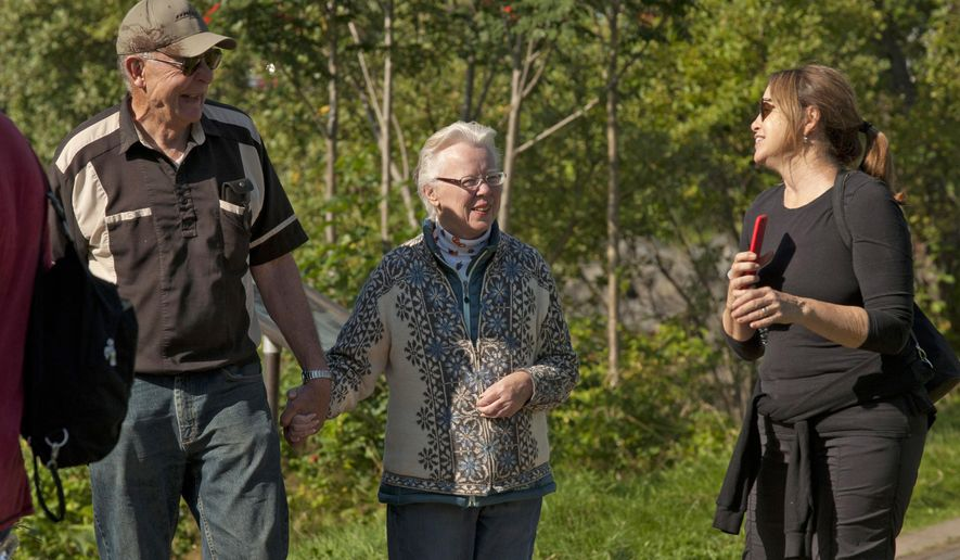 ADVANCE FOR WEEKEND SEPT. 16-17, 2017 AND THEREAFTER - In this Sept. 5, 2017 photo, Fred and Kathleen Everest, left and center, chat with Terri Maher, right, a tourist from Santa Barbara, Calif., on the Sea Walk in Sitka, Alaska. Conversations are not uncommon for Kathleen and Fred, who have become unofficial hosts for visitors exploring downtown. For the past two years, the Everest's have walked by the harbor on nearly every day when there's a cruise ship in port. (James Poulson/Sitka Sentinel via AP)