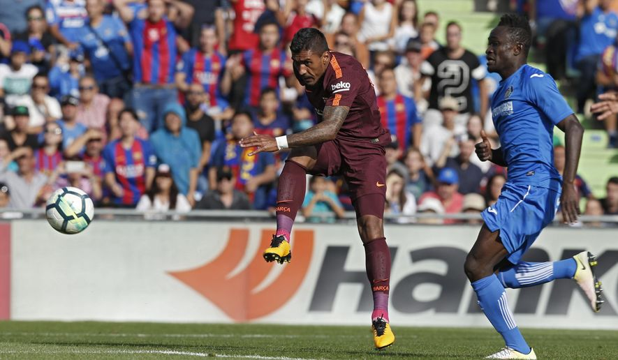 Barcelona's Paulinho, left, shoots to score the winning goal against Getafe during a Spanish La Liga soccer match between Getafe and Barcelona at the Alfonso Perez stadium in Getafe, outside Madrid, Saturday, Sept. 16, 2017.  (AP Photo/Francisco Seco)