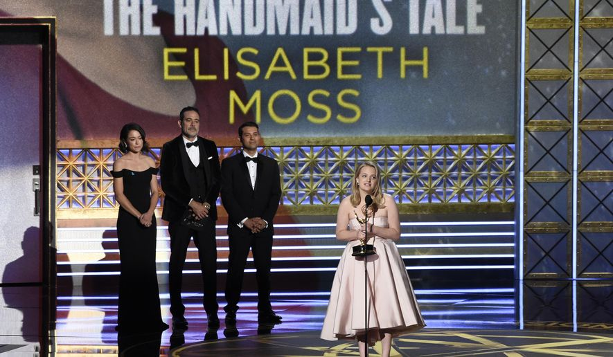 "Elisabeth Moss, center, accepts the award for outstanding lead actress in a drama series for ""The Handmaid's Tale"" while Tatiana Maslany, left, and Jeffrey Dean Morgan, right, look on at the 69th Primetime Emmy Awards on Sunday, Sept. 17, 2017, at the Microsoft Theater in Los Angeles. (Photo by Chris Pizzello/Invision/AP)"