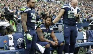 Seattle Seahawks defensive end Michael Bennett, center, is joined by teammates Thomas Rawls, left, and Justin Britt, right, as he sits during the singing of the national anthem before an NFL football game against the San Francisco 49ers, Sunday, Sept. 17, 2017, in Seattle. (AP Photo/Elaine Thompson)