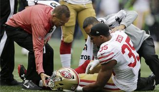 San Francisco 49ers strong safety Eric Reid (35) is tended to on the field after an injury in the first half of an NFL football game against the Seattle Seahawks, Sunday, Sept. 17, 2017, in Seattle. (AP Photo/John Froschauer)