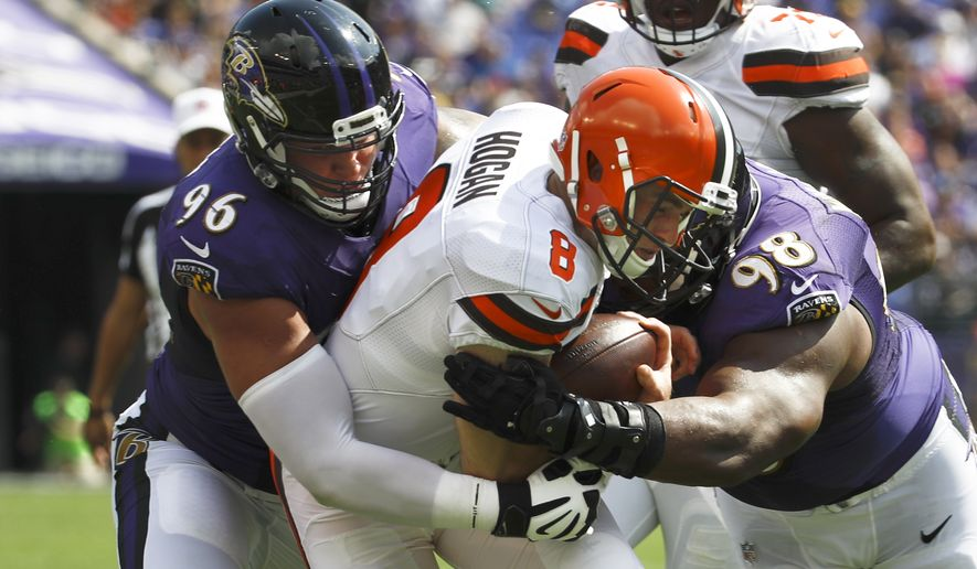 Cleveland Browns quarterback Kevin Hogan (8) is sandwiched between Baltimore Ravens defensive end Brent Urban (96) and Baltimore Ravens nose tackle Brandon Williams (98) during the first half of an NFL football game in Baltimore, Sunday, Sept. 17, 2017. (AP Photo/Patrick Semansky)