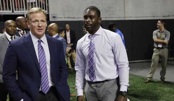 NFL Commissioner Roger Goodell, left, speaks with former NFL player Michael Vick on the turf before the first of an NFL football game between the Atlanta Falcons and the Green Bay Packers, Sunday, Sept. 17, 2017, in Atlanta. (AP Photo/David Goldman)