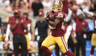 Washington Redskins running back Chris Thompson, left, scores against the Los Angeles Rams during the first half of an NFL football game Sunday, Sept. 17, 2017, in Los Angeles. (AP Photo/Kelvin Kuo)