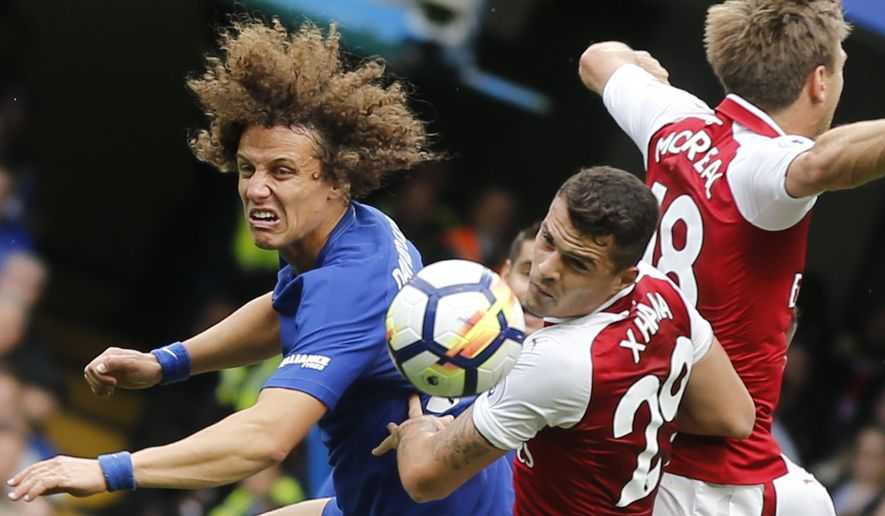 Chelsea's David Luiz, Arsenal's Granit Xhaka, and Arsenal's Nacho Monreal, from left, jump to head the ball during the English Premier League soccer match between Chelsea and Arsenal at Stamford Bridge stadium in London, Sunday, Sept. 17, 2017. (AP Photo/Frank Augstein)