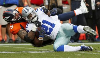 Dallas Cowboys running back Ezekiel Elliott (21) is tackled by Denver Broncos cornerback Chris Harris during the second half of an NFL football game, Sunday, Sept. 17, 2017, in Denver. (AP Photo/Jack Dempsey)