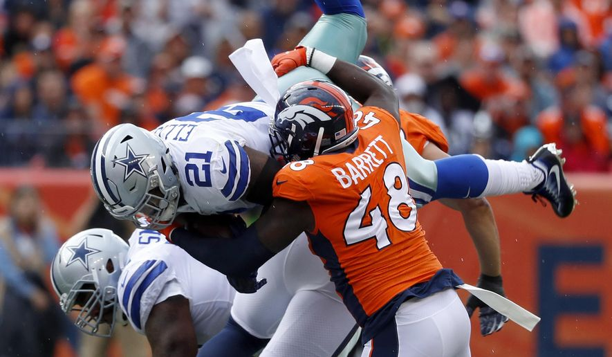 Dallas Cowboys running back Ezekiel Elliott (21) is hit by Denver Broncos outside linebacker Shaquil Barrett (48) during the first half of an NFL football game, Sunday, Sept. 17, 2017, in Denver. (AP Photo/Jack Dempsey)
