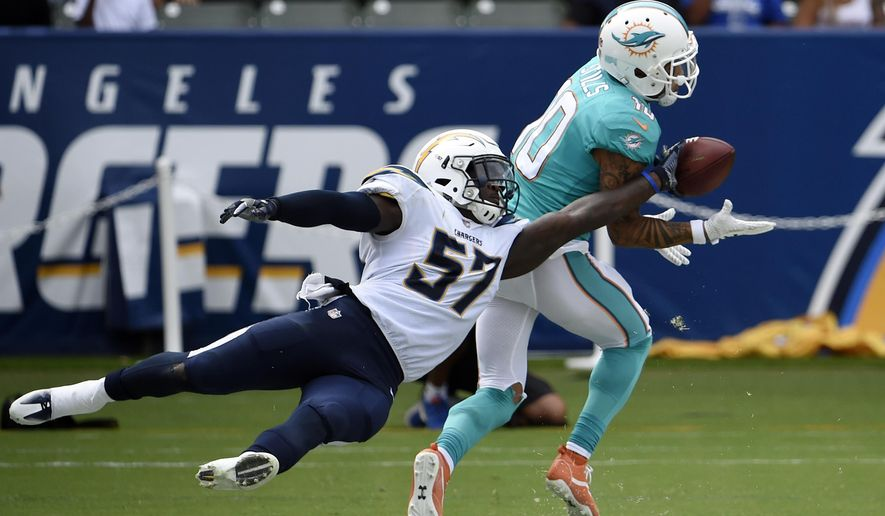 Miami Dolphins wide receiver Kenny Stills, right, makes a touchdown catch in the end zone as Los Angeles Chargers inside linebacker Jatavis Brown tries to get hand on the ball during the second half of an NFL football game Sunday, Sept. 17, 2017, in Carson, Calif. (AP Photo/Denis Poroy)