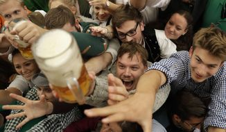 Young people struggle for beer during the opening of the 184th Oktoberfest beer festival in Munich, Germany, Saturday, Sept. 16, 2017. (AP Photo/Matthias Schrader) ** FILE **