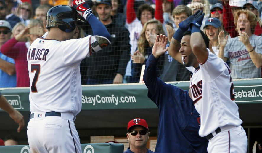 Minnesota Twins' Joe Mauer, left, is greeted by Eddie Rosario following Mauer's grand slam off Toronto Blue Jays relief pitcher Chris Rowley in the fifth inning of a baseball game Sunday, Sept. 17, 2017, in Minneapolis. (AP Photo/Jim Mone)