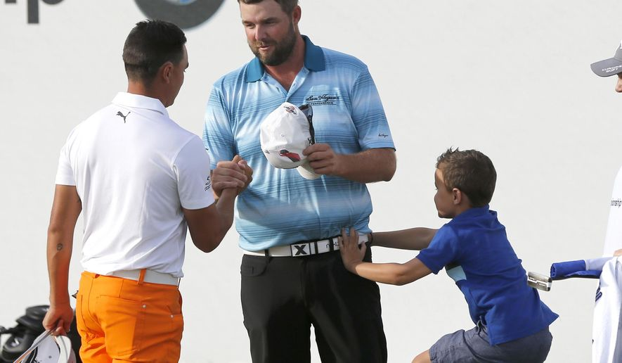 Marc Leishman, center, shakes hand with Rickie Fowler as Leishman's son Harvey jumps to his father after Leishman won the BMW Championship golf tournament at Conway Farms Golf Club, Sunday, Sept. 17, 2017, in Lake Forest, Ill. (AP Photo/Charles Rex Arbogast)