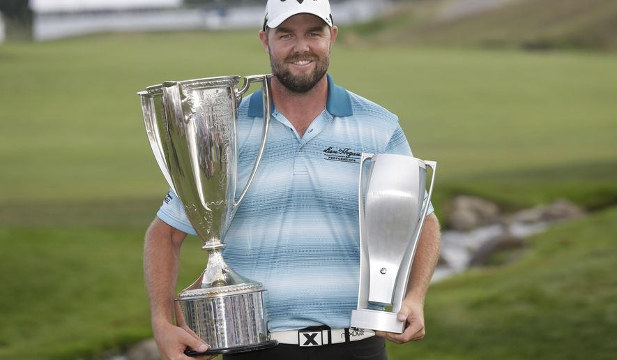 Marc Leishman smiles as he poses with the Wadley Cup, left, and the BMW Championship trophy after winning the BMW Championship golf tournament at Conway Farms Golf Club, Sunday, Sept. 17, 2017, in Lake Forest, Ill. (AP Photo/Charles Rex Arbogast)