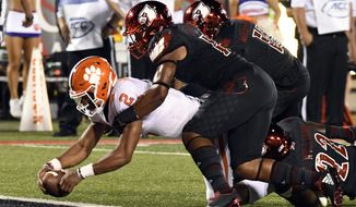 Clemson quarterback Kelly Bryant (2) is brought down by Louisville's Dorian Etheridge, front right, and Trumaine Washington (15) as he crosses the goal line during the first half of an NCAA college football game, Saturday, Sept. 16, 2017, in Louisville, Ky. (AP Photo/Timothy D. Easley)