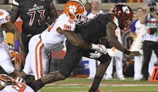 Louisville's Lamar Jackson (8) is wrapped up by Clemson's Clelin Ferrell (99) during the first half of an NCAA college football game, Saturday, Sept. 16, 2017, in Louisville, Ky. (AP Photo/Timothy D. Easley)