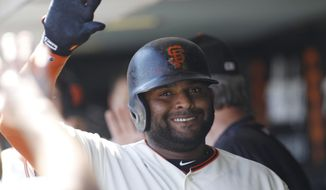 San Francisco Giants' Pablo Sandoval is greeted in the dugout after hitting a sacrifice fly to score Austin Slater during the fourth inning of a baseball game against the Arizona Diamondbacks, Sunday, Sept. 17, 2017, in San Francisco. (AP Photo/George Nikitin)