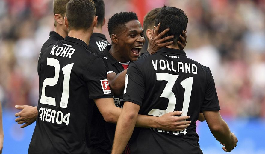 Leverkusen's scorer Kevin Volland, right, and his teammate Wendell, center, celebrate their side's 3rd goal during the German Bundesliga soccer match between Bayer 04 Leverkusen and SC Freiburg in Leverkusen, Germany, Sunday, Sept. 17, 2017. (Federico Gambarini/dpa via AP)