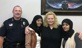 In this July 2017, photo provided by the Fargo Police Department, Police Chief David Todd, left, poses with, second from left, Sarah Hassan, Amber Hensley, center, and Leyla Hassan in Fargo, N.D. The three were involved in a verbal confrontation in a Walmart parking lot in Fargo, N.D. The dispute was quickly diffused just a few days later, with the women meeting in the police chief's office for hugs and a posed, smiling photo. It was one of the uglier incidents in Fargo race relations. Human rights groups in North Dakota are pushing for a comprehensive hate crimes law following the incident. (Fargo Police Department via AP)