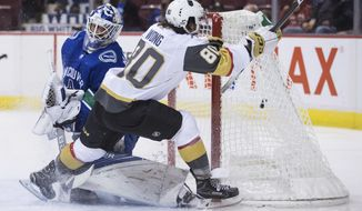 Vegas Golden Knights' Tyler Wong (80) scores his first goal against Vancouver Canucks' goalie Richard Bachman during the first period of a preseason NHL hockey game in Vancouver, British Columbia, Sunday, Sept. 17, 2017. (Darryl Dyck/The Canadian Press via AP)