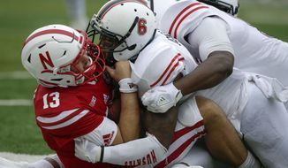 Northern Illinois defensive tackle Ben LeRoy (99) and linebacker Bobby Jones IV (6) sack Nebraska quarterback Tanner Lee (13) during the second half of an NCAA college football game in Lincoln, Neb., Saturday, Sept. 16, 2017. Northern Illinois won 21-17. (AP Photo/Nati Harnik)