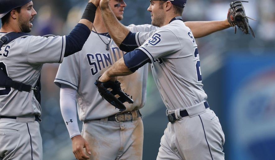 San Diego Padres catcher Austin Hedges, left, congratulates left fielder Matt Szczur, right, as first baseman Wil Myers, back, looks to other teammates after Colorado Rockies' Charlie Blackmon popped out for the final out in the ninth inning of a baseball game Sunday, Sept. 17, 2017, in Denver. (AP Photo/David Zalubowski)