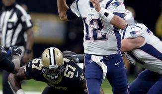 New England Patriots quarterback Tom Brady (12) passes under pressure from New Orleans Saints defensive end Alex Okafor (57) in the first half of an NFL football game in New Orleans, Sunday, Sept. 17, 2017. (AP Photo/Bill Feig)